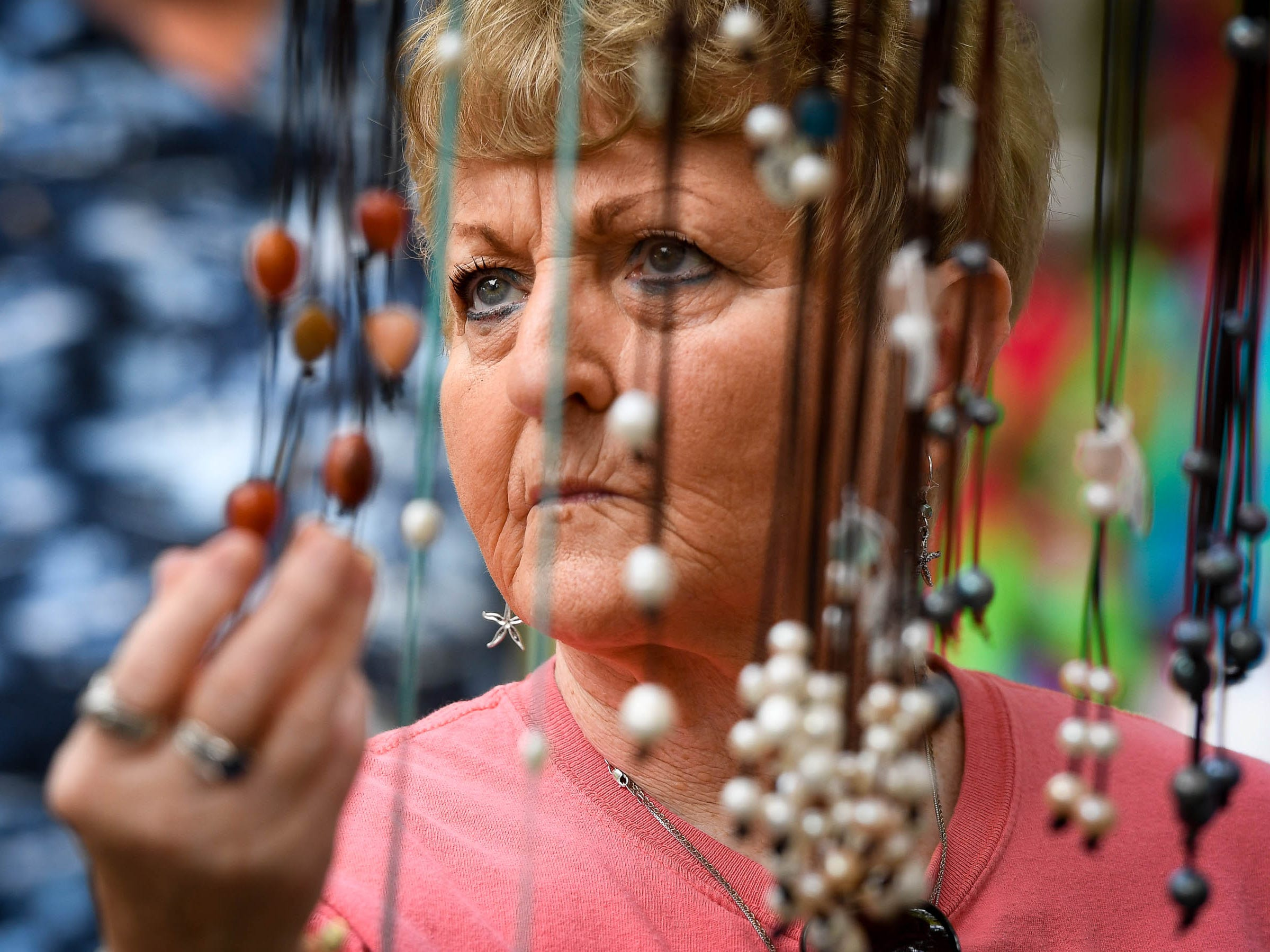 Linda Kimsey looks at necklaces as she browses the vendor booths at the Henderson Lions Arts and Crafts festival held at Audubon State Park Saturday, October 6, 2018.