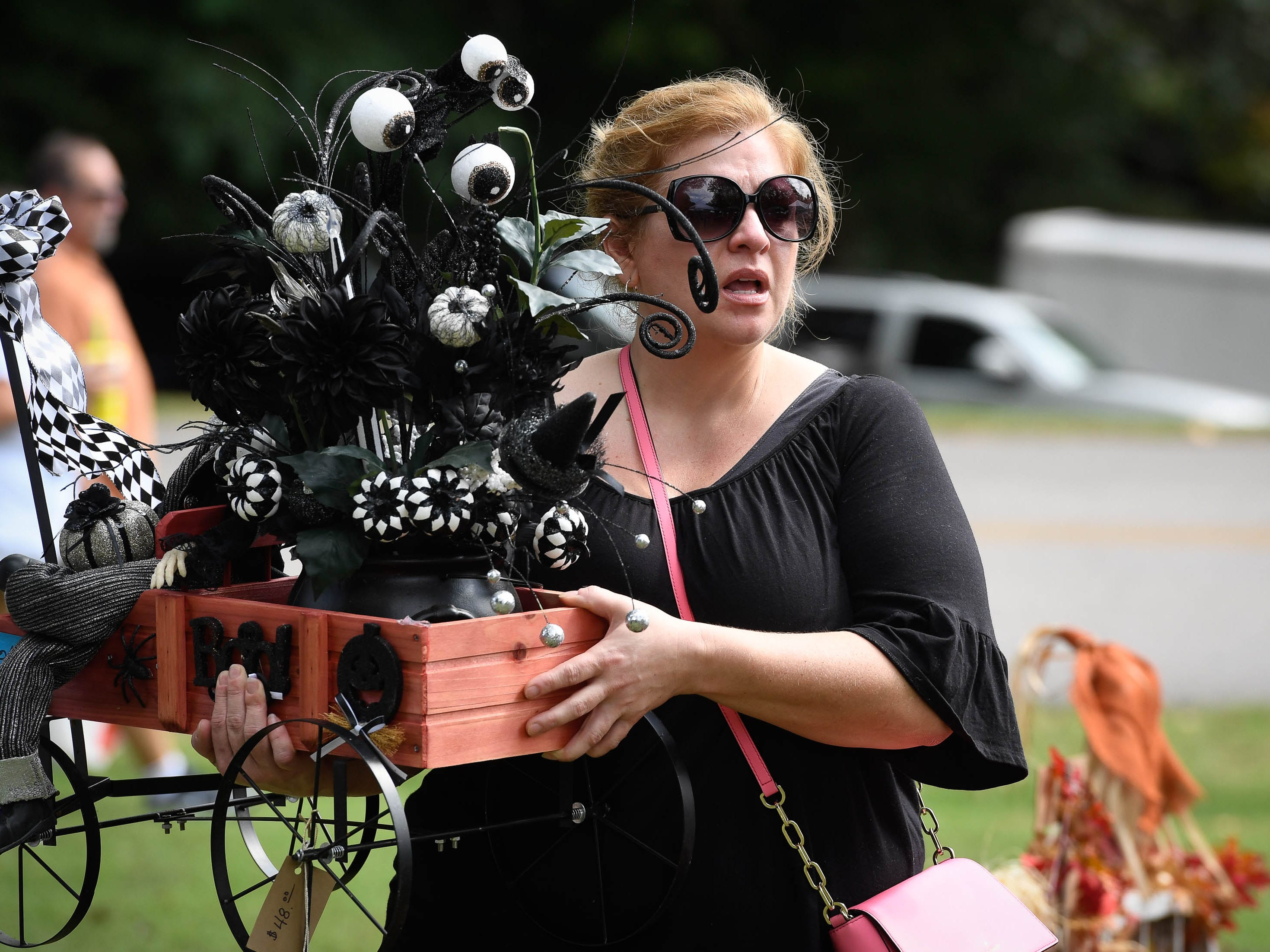 Carrying a Halloween themed center piece, Rachel Hale, Sebree, Ky., looks for more bargains at the Henderson Lions Arts and Crafts festival held at Audubon State Park Saturday. The event, with nearly 100 vendors selling everything from seasonal florals to iron work, continues Sunday 10 a.m. to 4 p.m. October 6, 2018.