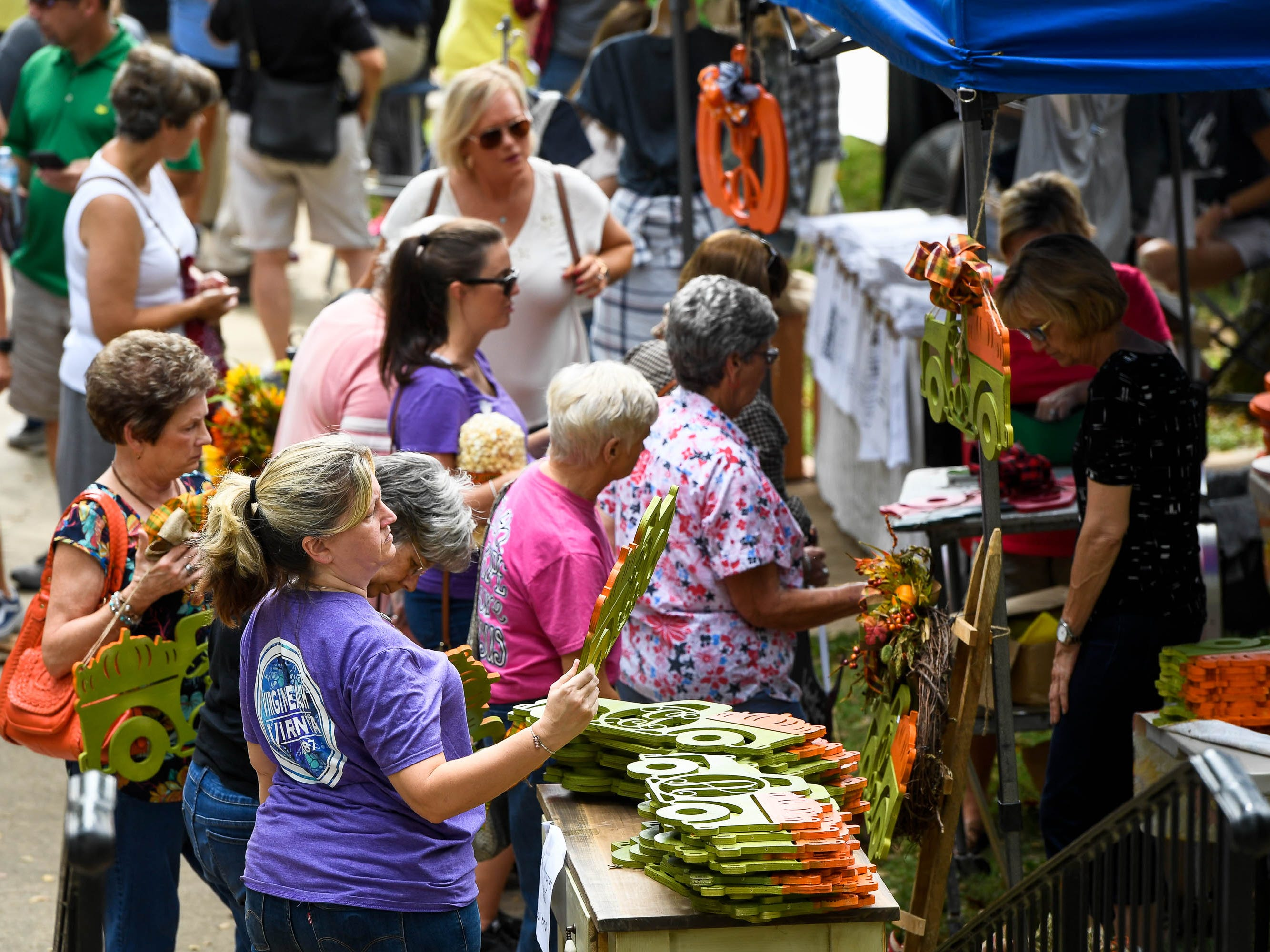 Eager crafts shoppers pour through the vendors booths at the Henderson Lions Arts and Crafts festival held at Audubon State Park Saturday. The event, with nearly 100 vendors selling everything from seasonal florals to iron work, continues Sunday 10 a.m. to 4 p.m. October 6, 2018.
