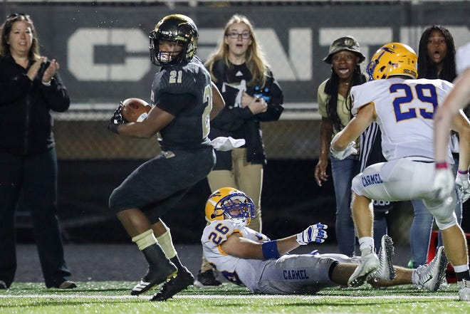 Warren Central Warriors Romeir Elliott (21) jukes away from Carmel Greyhounds defenders in the second half of the game at Warren Central High School, Indianapolis, Ind., Friday, Oct. 5, 2018. Warren Central won, 41-17.