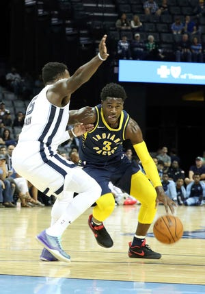 Indiana Pacers Aaron Holiday (3) drives the ball past Memphis Grizzlies Shelvin Mack (6) in the first half of a preseason NBA basketball game Saturday, Oct. 6, 2018, in Memphis, Tenn. (AP Photo/Karen Pulfer Focht)
