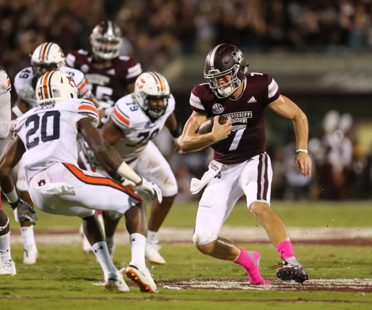 Mississippi State's Nick Fitzgerald (7) makes a move on Auburn's Jeremiah Dinson (20) in the second quarter. Mississippi State and Auburn played in an SEC college football game on Saturday, October 6, 2018, in Starkville.
