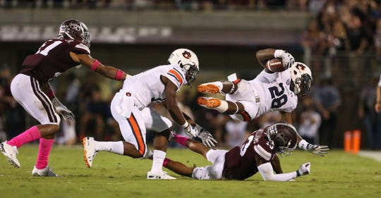 The Mississippi State defense closes in on Auburn's JaTarvious Whitlow (28). Mississippi State and Auburn played in an SEC college football game on Saturday, October 6, 2018, in Starkville.