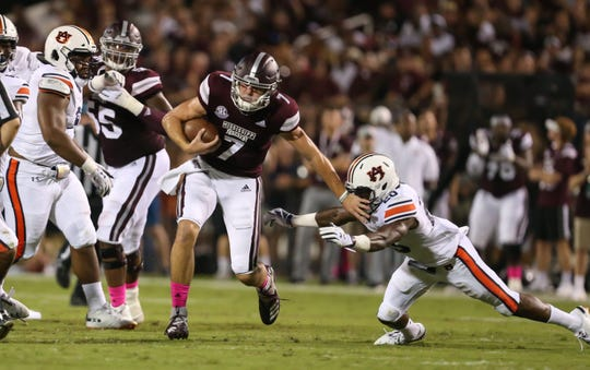 Mississippi State's Nick Fitzgerald (7)  eludes Auburn's Jeremiah Dinson (20) in the first quarter. Mississippi State and Auburn played in an SEC college football game on Saturday, October 6, 2018, in Starkville.