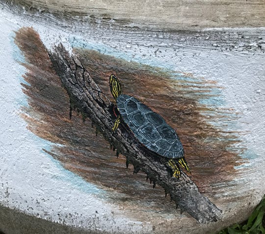 A turtle climbs a branch on a portion of a mural Dan Wiles is painting on a concrete cistern at Mill Pointe Park in Eaton Rapids.