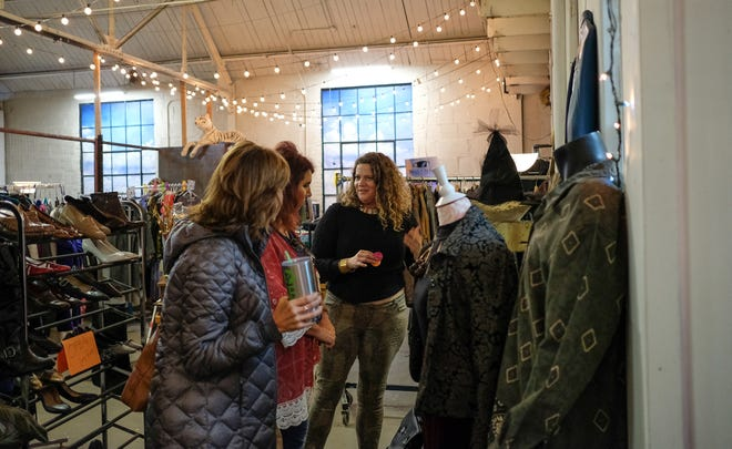 Tiffany Lemieux-McKissic, right, owner of Blue Onyx Thrift in the Reo Town Marketplace talks with customers Saturday, Oct. 6, 2018.