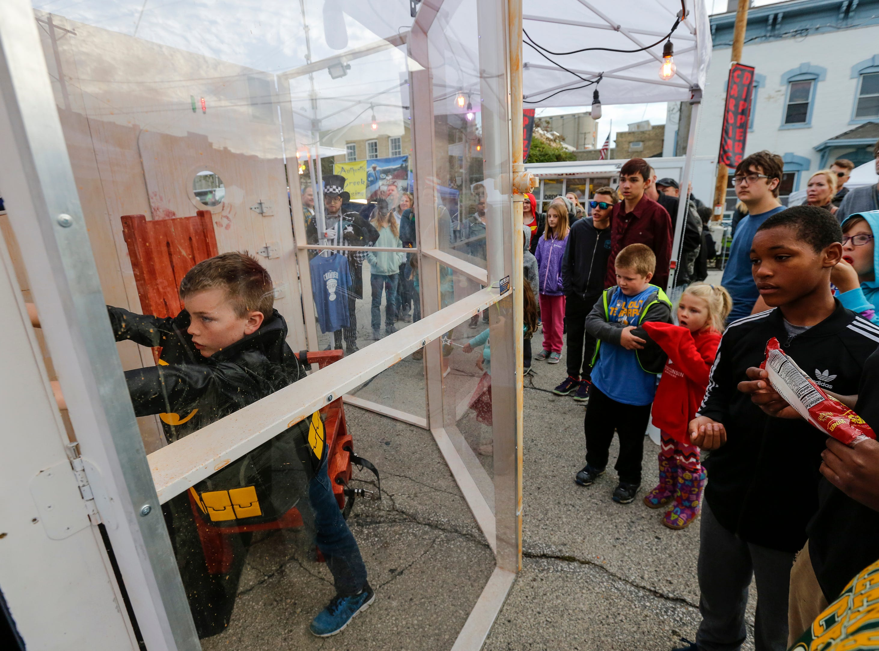Landon Brice, 10, of Manitowoc tries to get out of a portable escape room built by What the Lock? as people cheer him on during Windigo Fest on Saturday, Oct. 6, 2018, in Manitowoc, Wis.