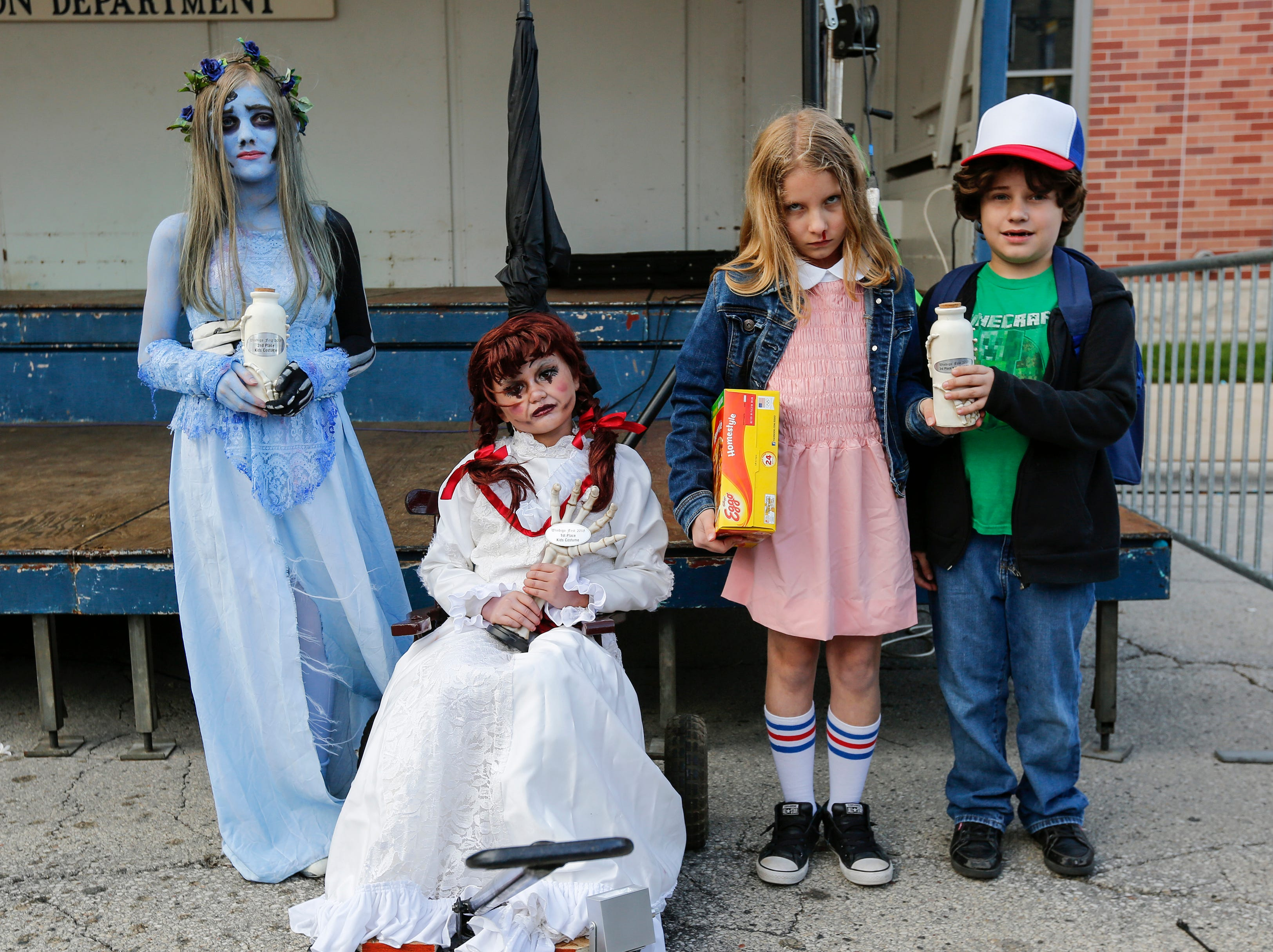 Winners of the children's costume contest from left, Dilin Kane, 11, as corpse bride; Chloe Schroeder, 9, dressed as Annabelle; and siblings Jillian, 11, and Jakob Hoffmann, 8, pose in their costumes during Windigo Fest Saturday, Oct. 6, 2018, in Manitowoc, Wis.
