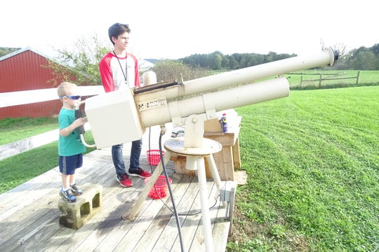 Weston Lacey, 3, of Butler, prepares to fire an apple cannon Saturday as his older cousin looks on.