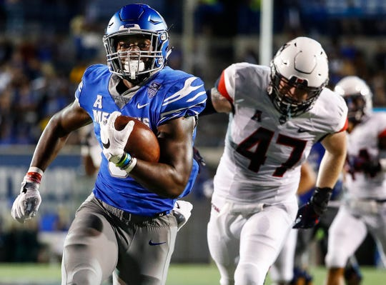 Memphis running back Patrick Taylor Jr. (left) runs past the UConn defender Santana Sterling (right) on his way to a touchdown during action in Memphis, Tenn., Saturday, October 6, 2018.
