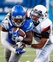 Memphis running back Darrell Henderson (left) runs past the UConn defender Tyler Coyle (right) during action in Memphis, Tenn., Saturday, October 6, 2018.