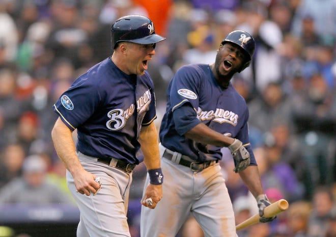 Lorenzo Cain and Erik Kratz celebrate after Kratz scores a run in the sixth inning.