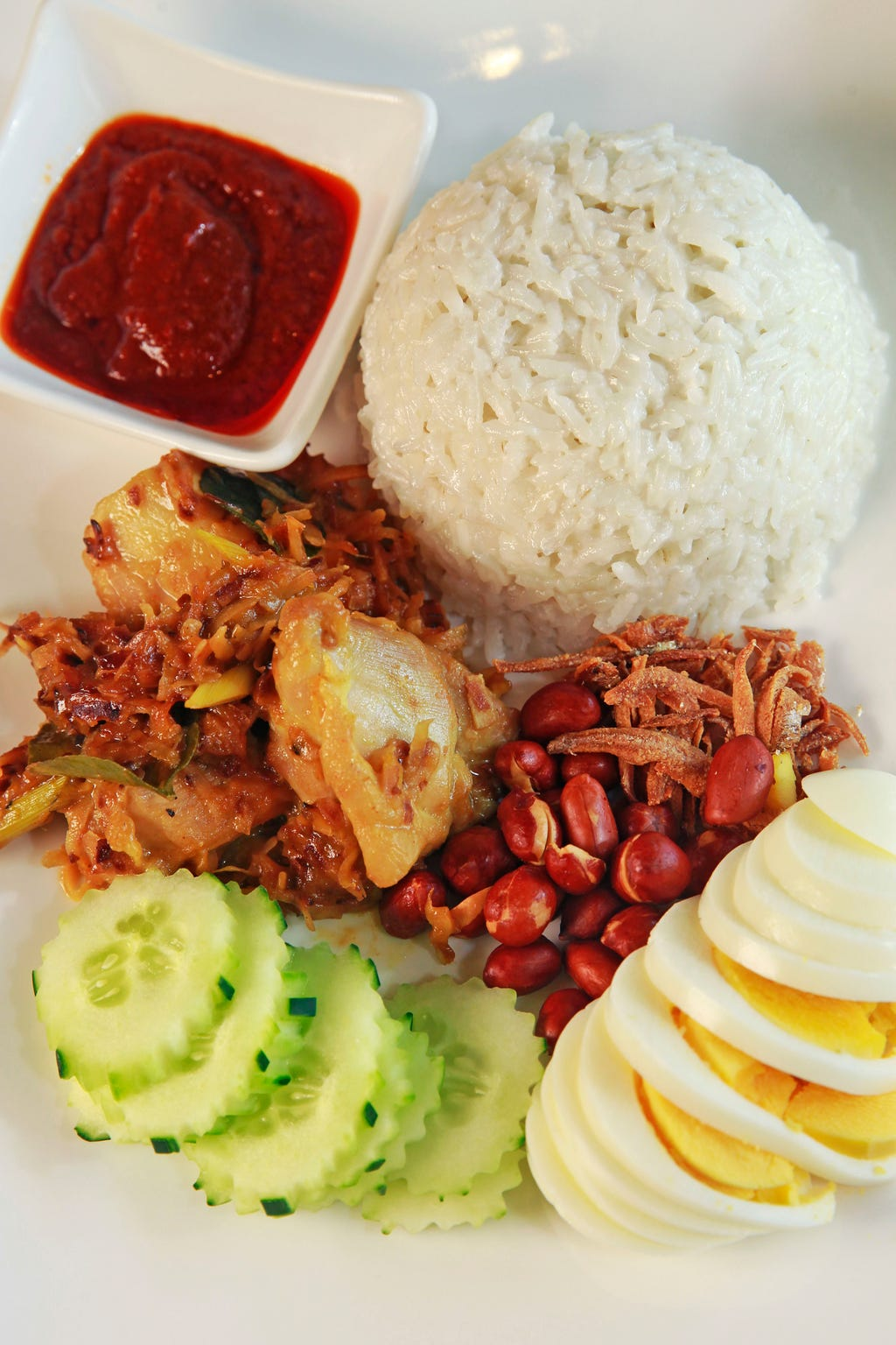 Nasi lemak is coconut-flavored rice with eggs, cucumber and sambal chile sauce. It's shown here with chicken but also served with beef at  Mr. Wok Pan-Asian Cuisine, 2128 Silvernail Road, Pewaukee.