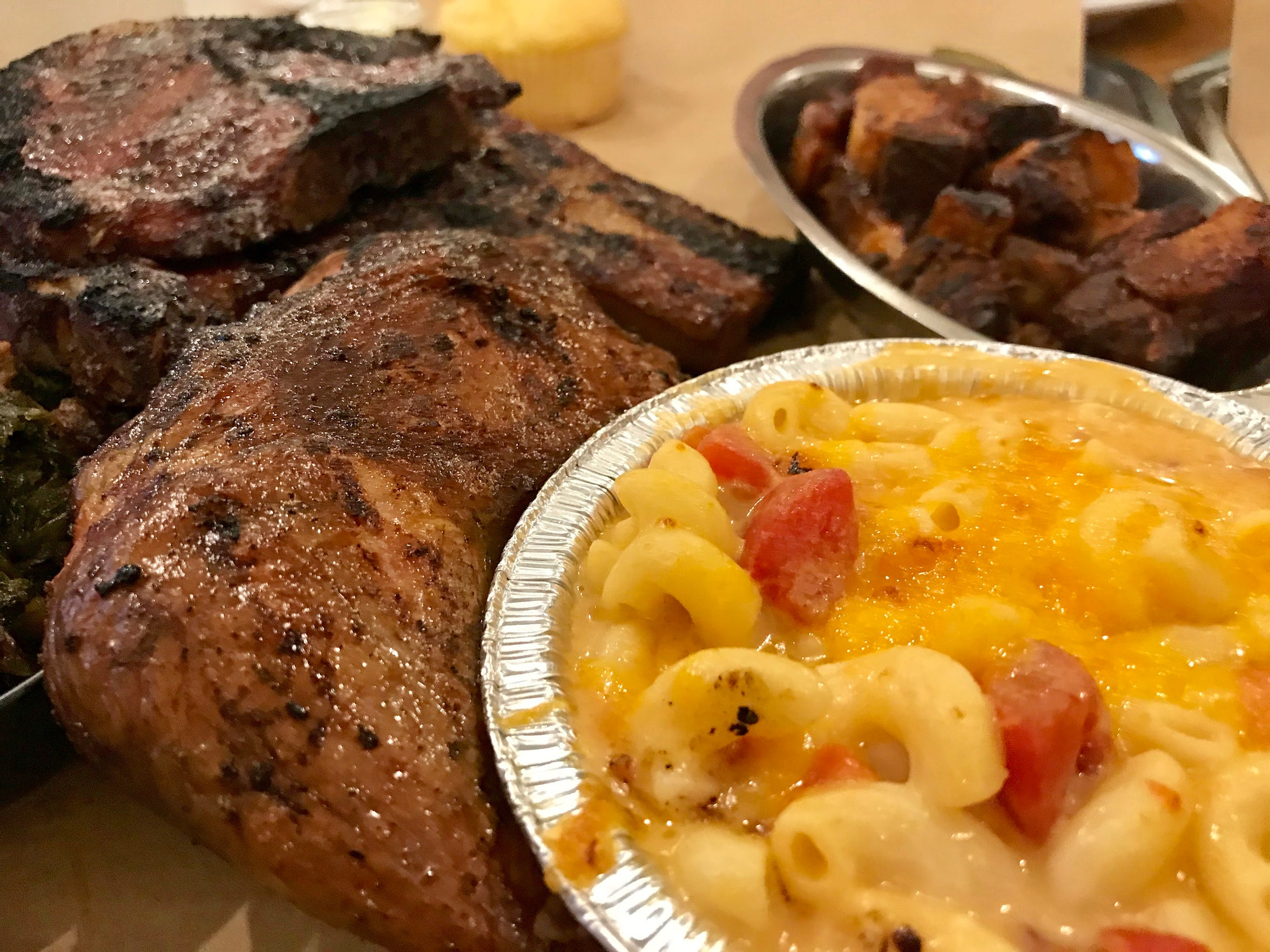 """Iron Grate BBQ Co., 4125 S. Howell Ave., serves a variety of wood-smoked meats as well as side dishes that involve smoke in some way, such as (from right) mac and cheese with smoked tomato, chicken leg quarter and a special, the """"pile o' pork chops."""""""