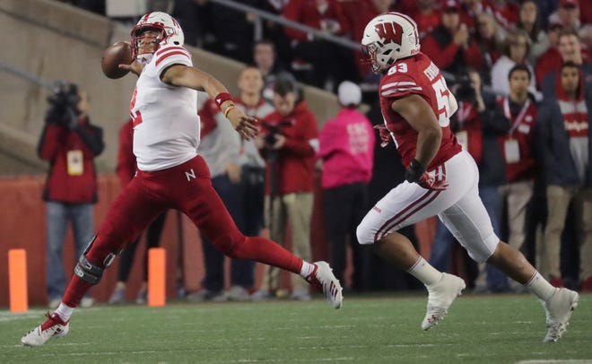 Nebraska quarterback Adrian Martinez gets ready to heave a pass downfield as he's being chased by Badgers inside linebacker T.J. Edwards during the first quarter on Saturday night.