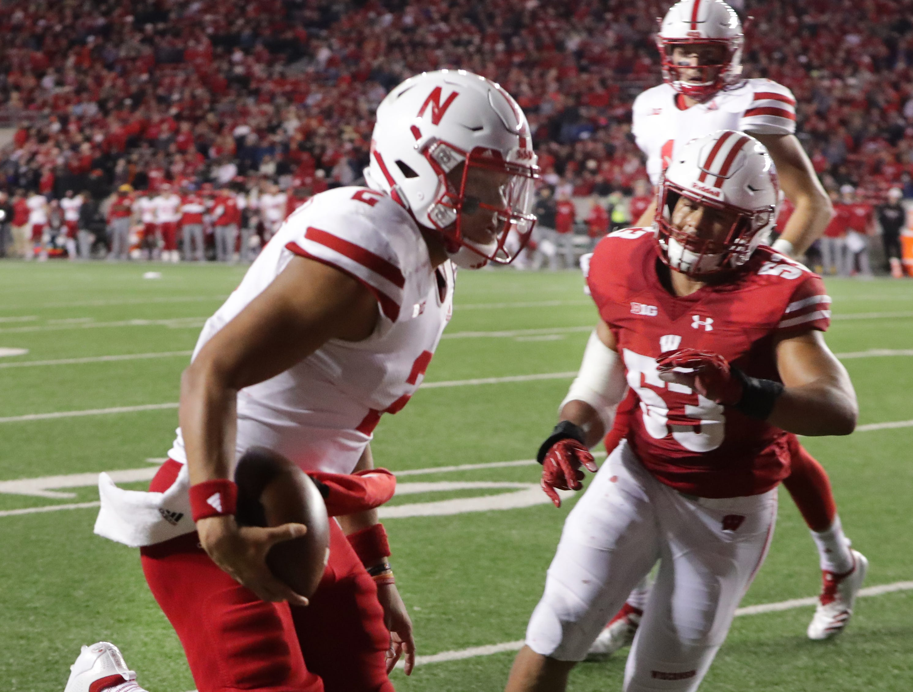 Nebraska quarterback Adrian Martinez outruns UW inside linebacker T.J. Edwards on a 7-yard touchdown scamper during the fourth quarter Saturday night.