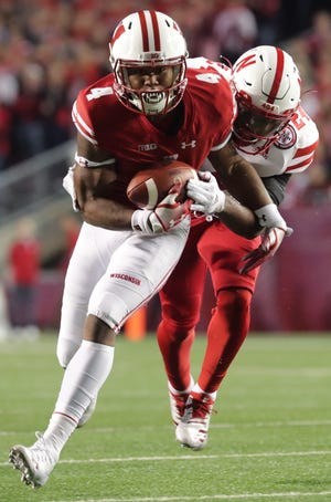 Wisconsin wide receiver A.J. Taylor picks up 14 yards and a first down on a reception despite the effort of Nebraska defensive back Aaron Williams during the second quarter on Saturday night.