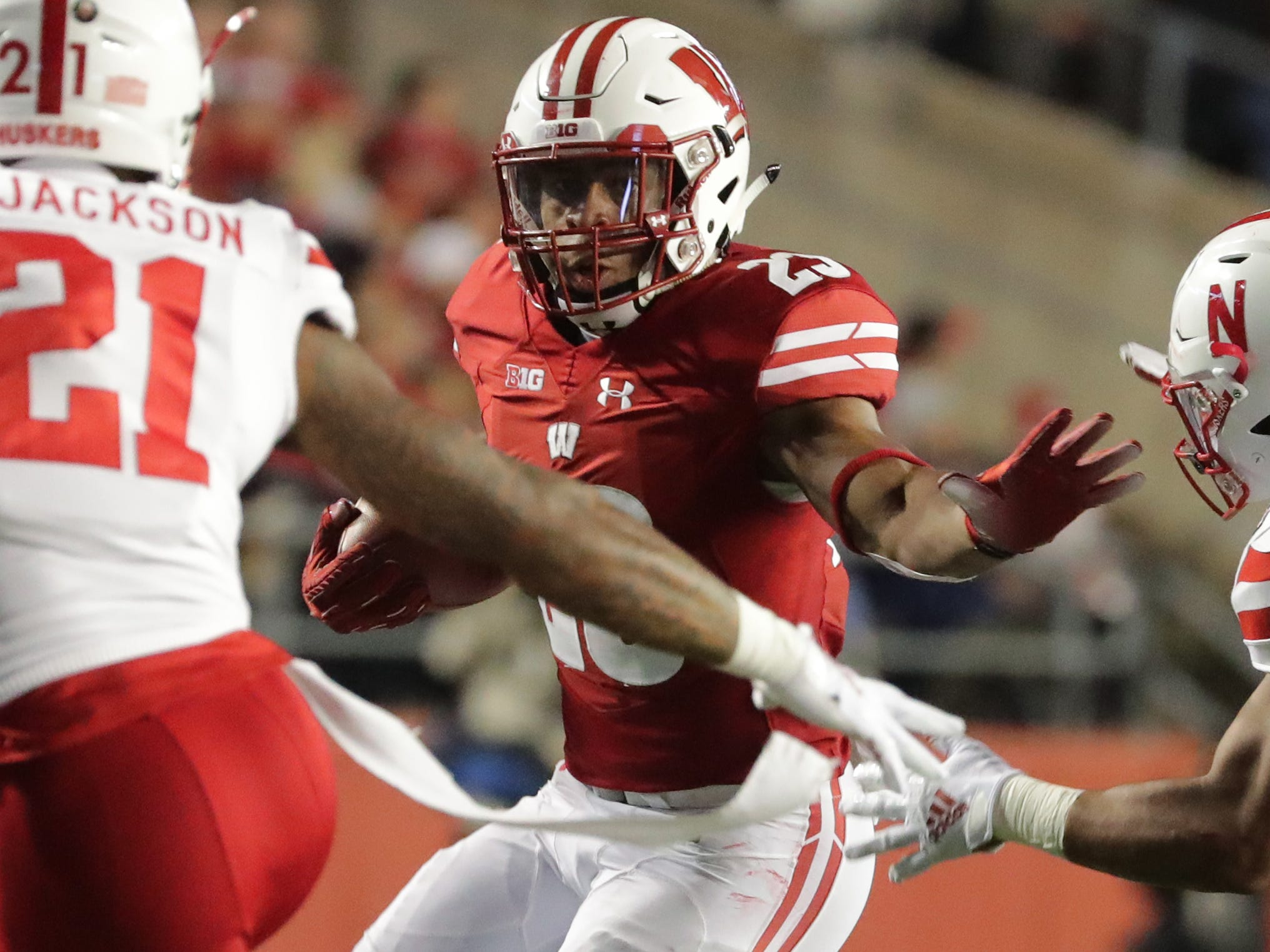 Wisconsin running back Jonathan Taylor is pursued by Nebraska defensive back Lamar Jackson and linebacker Dedrick Young II during the third quarter on Saturday night.