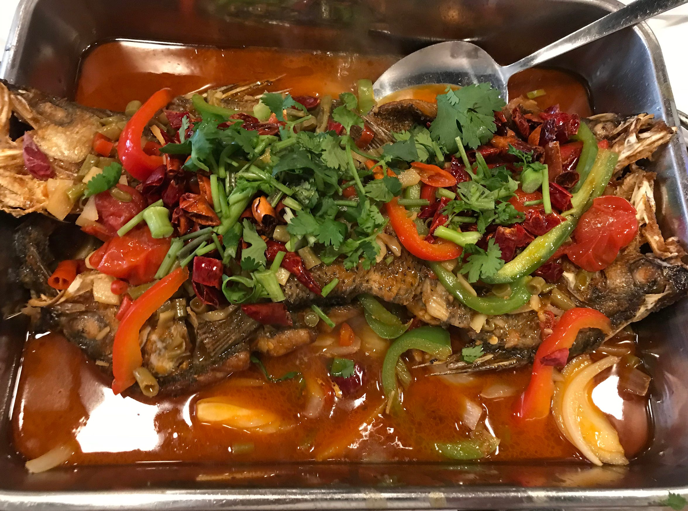 Beer-braised fish, a special that is smothered in sweet and hot peppers and cilantro, is kept warm in a steel hotpot over a flame at the table. It's served at Asian Fusion, 1609 E. North Ave.