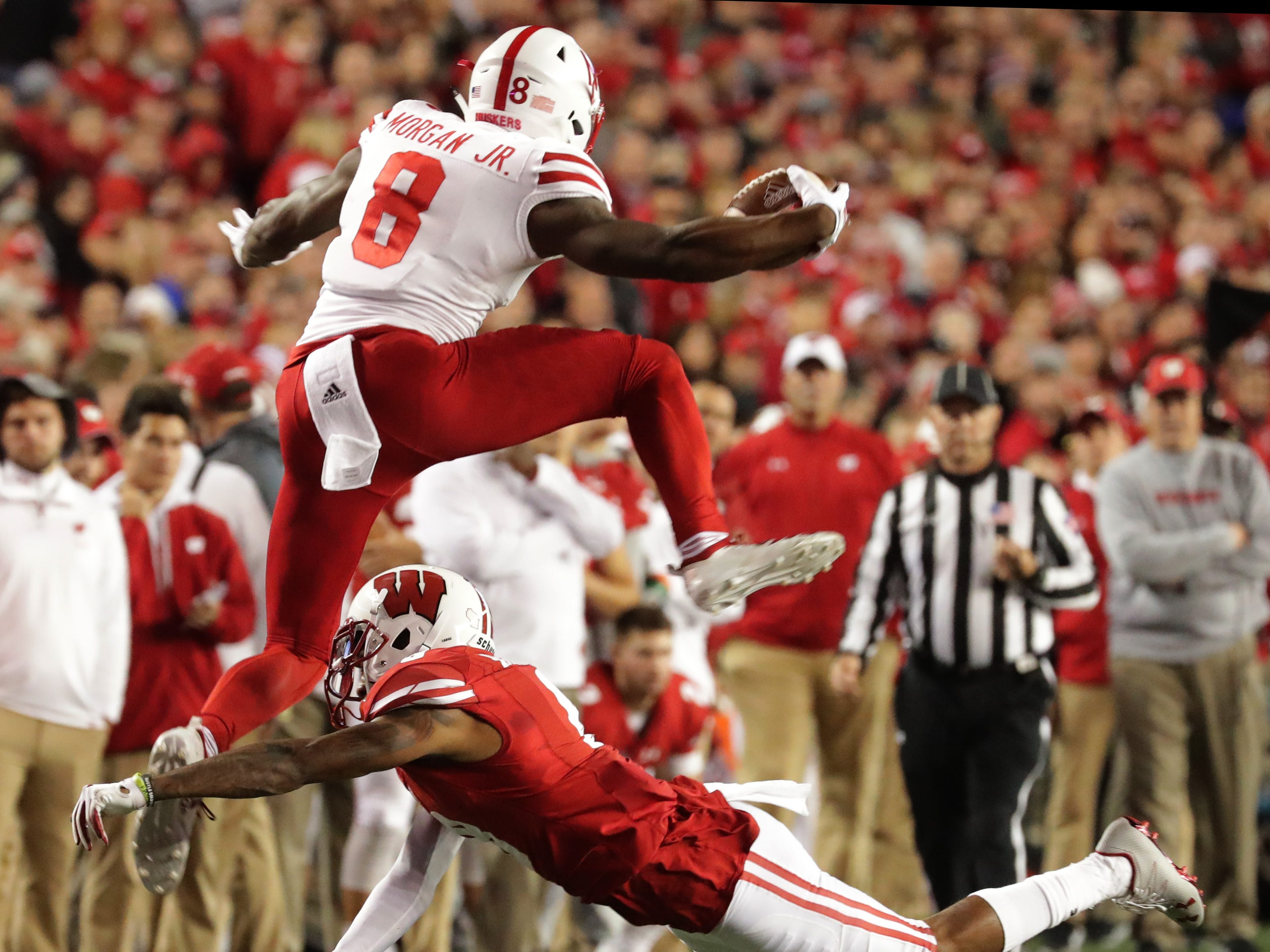 Nebraska wide receiver Stanley Morgan Jr. hurdles Wisconsin cornerback Deron Harrell to pick up a few extra yards and a first down during the second quarter Saturday night at Camp Randall Stadium.