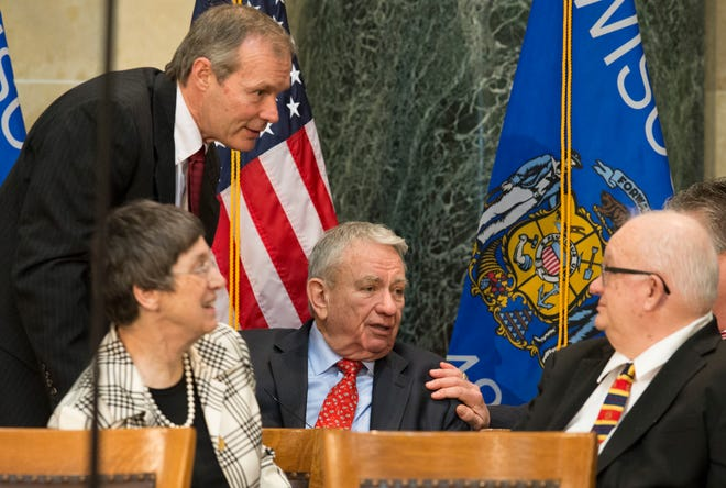 Former Gov. Scott McCallum (standing) and Tommy Thompson (center) speak with Llewellyn Walker, father of Gov. Scott Walker, during the inaugural ceremonies for constitutional officers in January 2014.