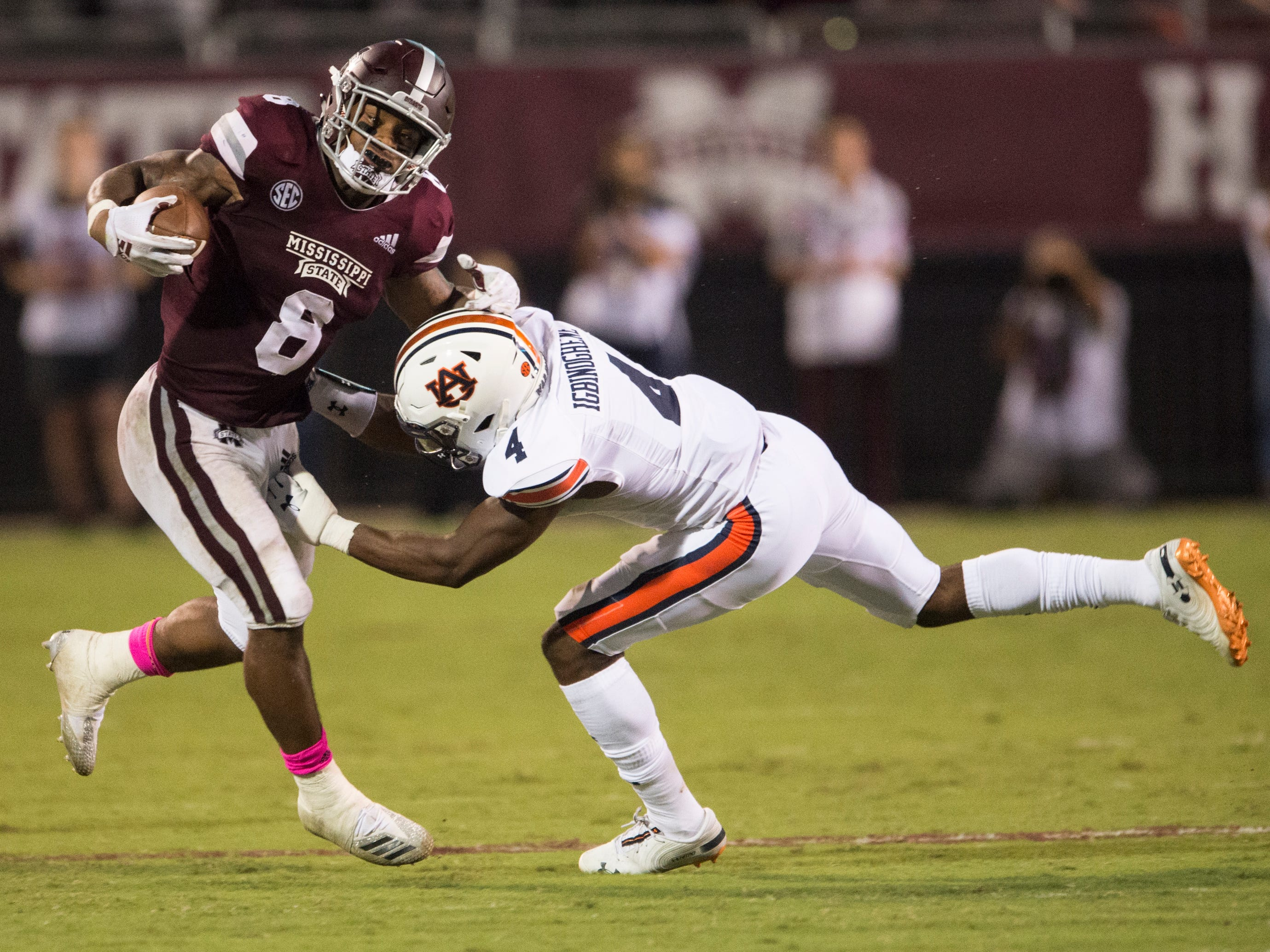 Mississippi State's Kylin Hill (8) is pushed out of bounds by Auburn's Noah Igbinoghene (4) at Davis Wade Stadium in Starkville, Miss., on Saturday, Oct. 6, 2018. Mississippi State defeated Auburn 23-9.