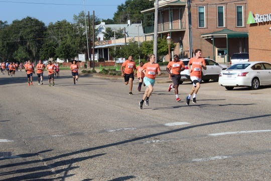 "Leaders in Saturday's annual ""Run for Kenya"" turn the corner in downtown Selma Saturday morning."