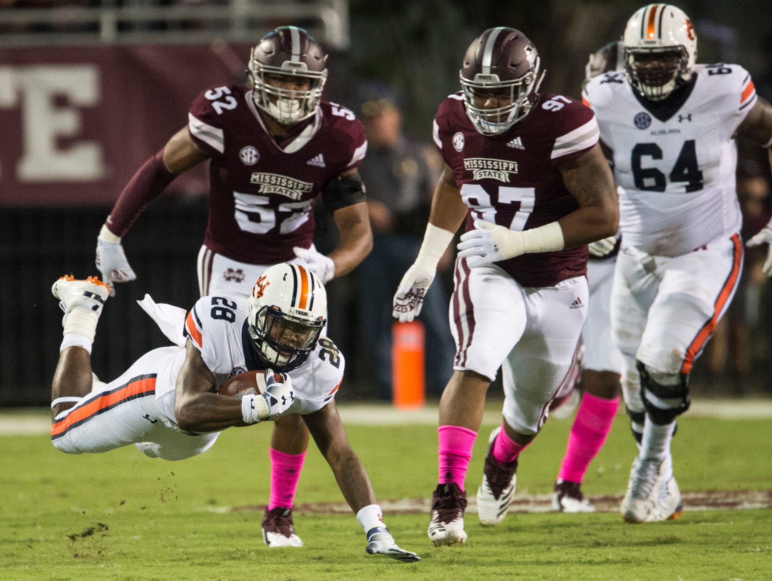 Auburn's JaTarvious Whitlow (28) falls forward for a few extra yards against Mississippi State at Davis Wade Stadium in Starkville, Miss., on Saturday, Oct. 6, 2018. Mississippi State leads Auburn 13-3 at halftime.