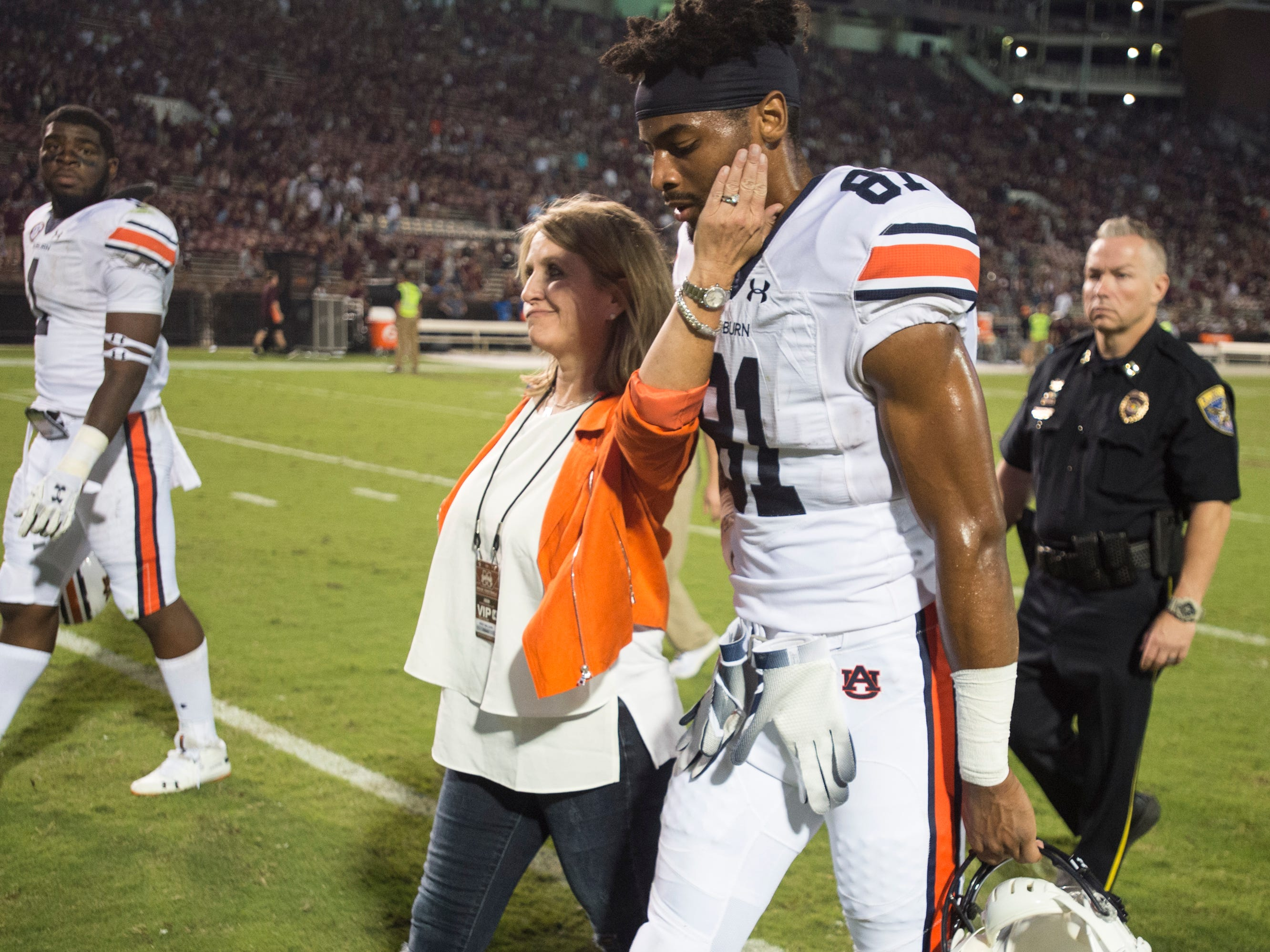 Kristi Malzahn, wife of Auburn head coach Gus Malzahn, comforts Auburn's Darius Slayton (81) as they walk off the field after the game at Davis Wade Stadium in Starkville, Miss., on Saturday, Oct. 6, 2018. Mississippi State defeated Auburn 23-9.