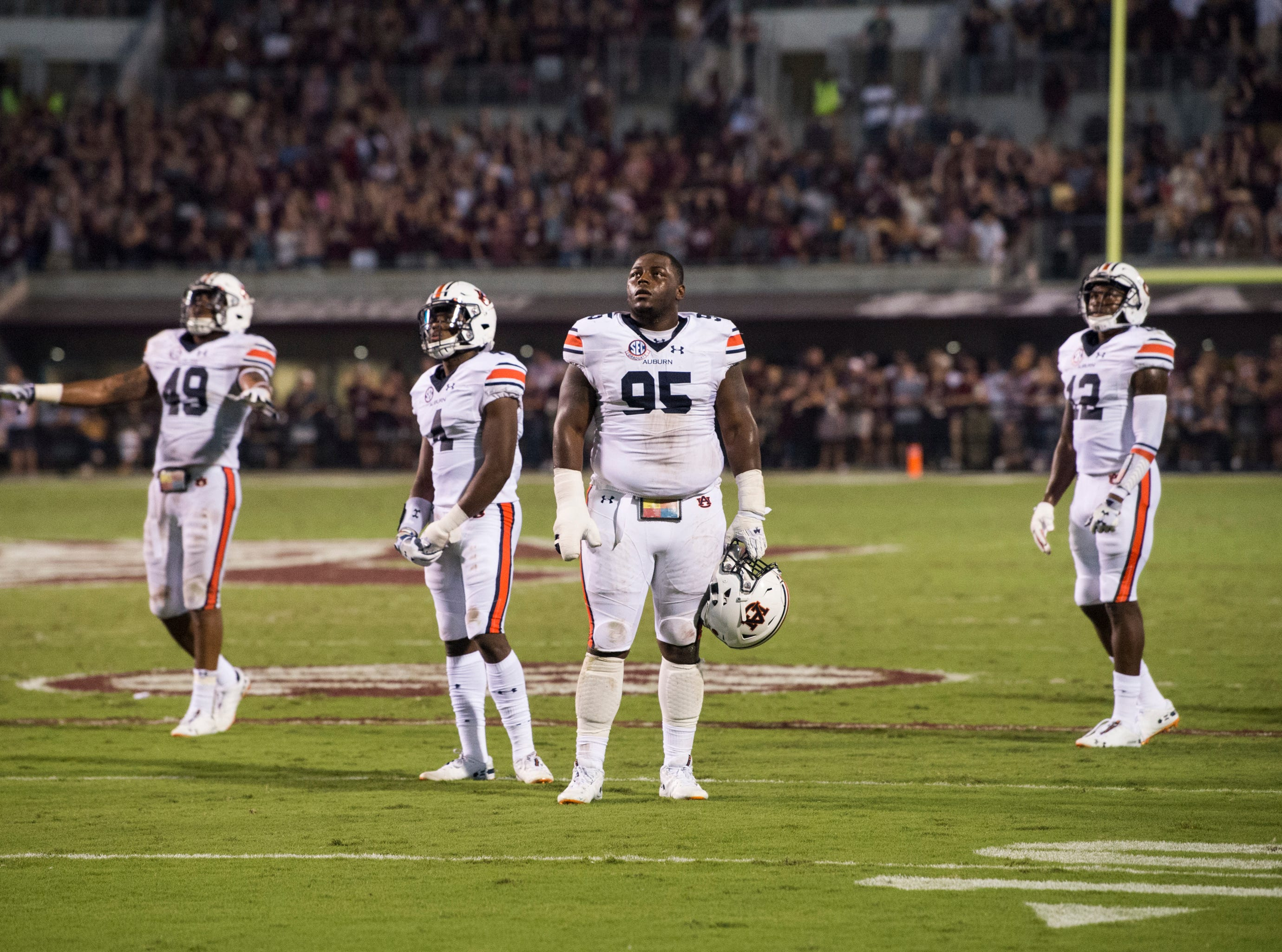 Auburn defense players watch the big screen as the officials review a Mississippi State touchdown at Davis Wade Stadium in Starkville, Miss., on Saturday, Oct. 6, 2018. Mississippi State leads Auburn 13-3 at halftime.