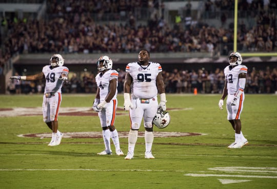 Auburn defensive players watch the big screen as the officials review a Mississippi State touchdown at Davis Wade Stadium in Starkville, Miss., on Saturday, Oct. 6, 2018.