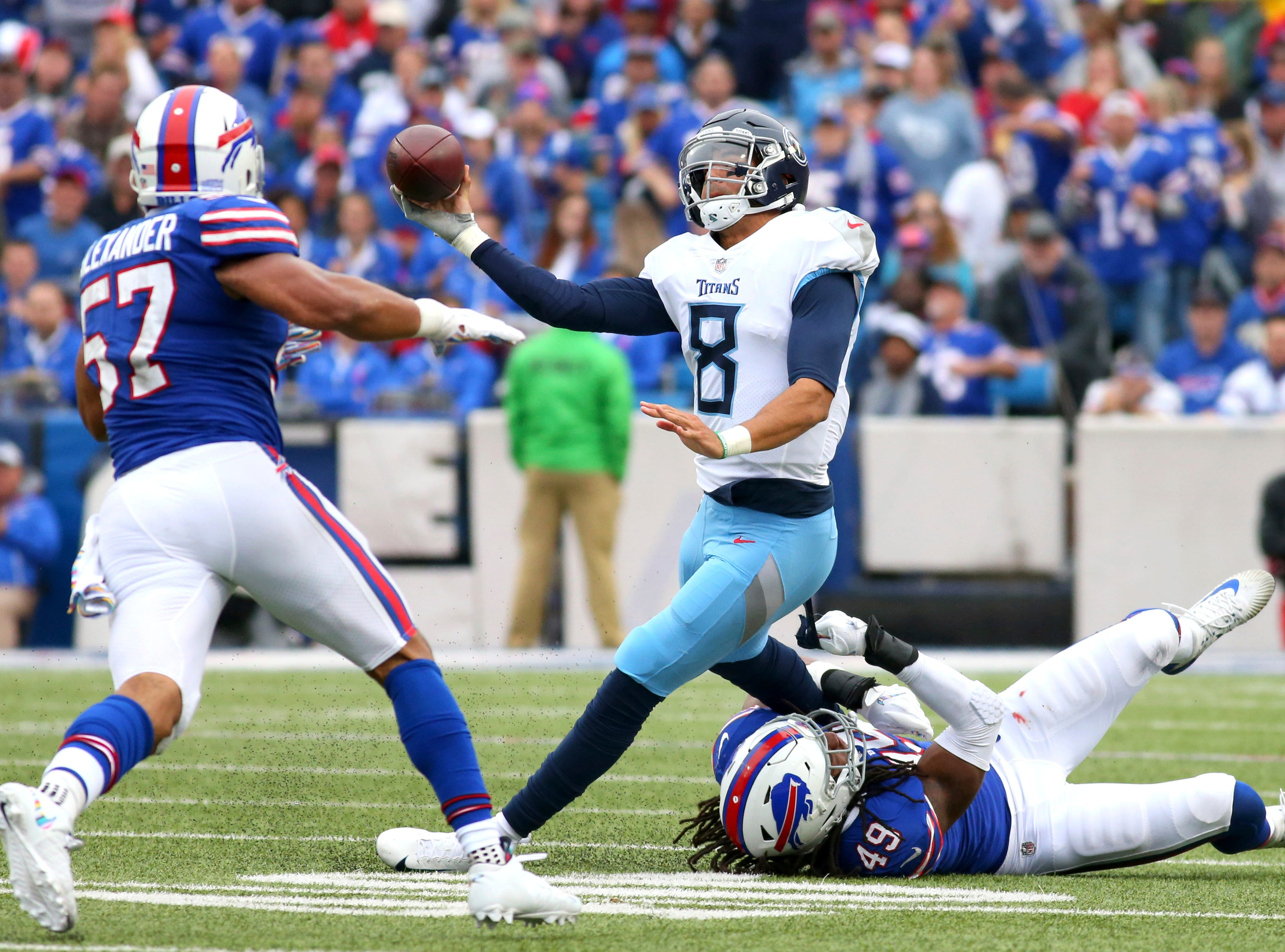 Tennessee Titans quarterback Marcus Mariota (8) tries to make a pass as Buffalo Bills linebacker Tremaine Edmunds (49) makes the hit during the second half of an NFL football game, Sunday, Oct. 7, 2018, in Orchard Park, N.Y. Bills' Lorenzo Alexander (57) helps defend on the play. (AP Photo/Jeffrey T. Barnes)