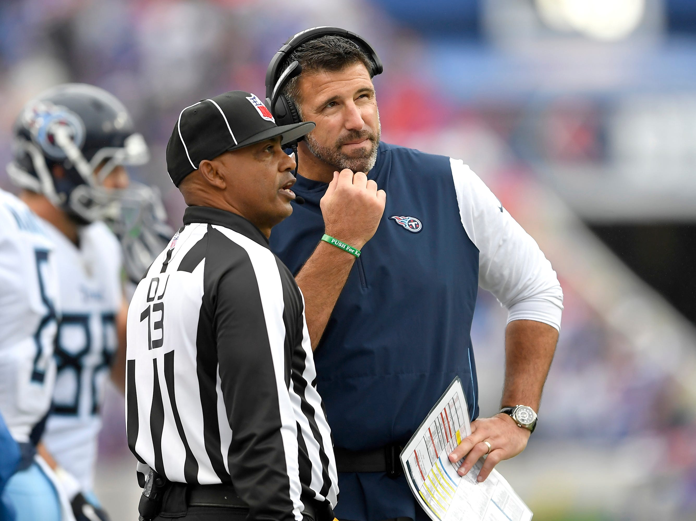 Tennessee Titans head coach Mike Vrabel, right, talks to head linesman Patrick Turner (13) during the first half of an NFL football game against the Buffalo Bills, Sunday, Oct. 7, 2018, in Orchard Park, N.Y. (AP Photo/Adrian Kraus)