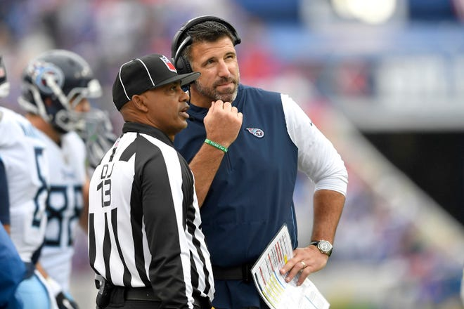 Titans coach Mike Vrabel, right, talks to head linesman Patrick Turner during the first half Sunday.