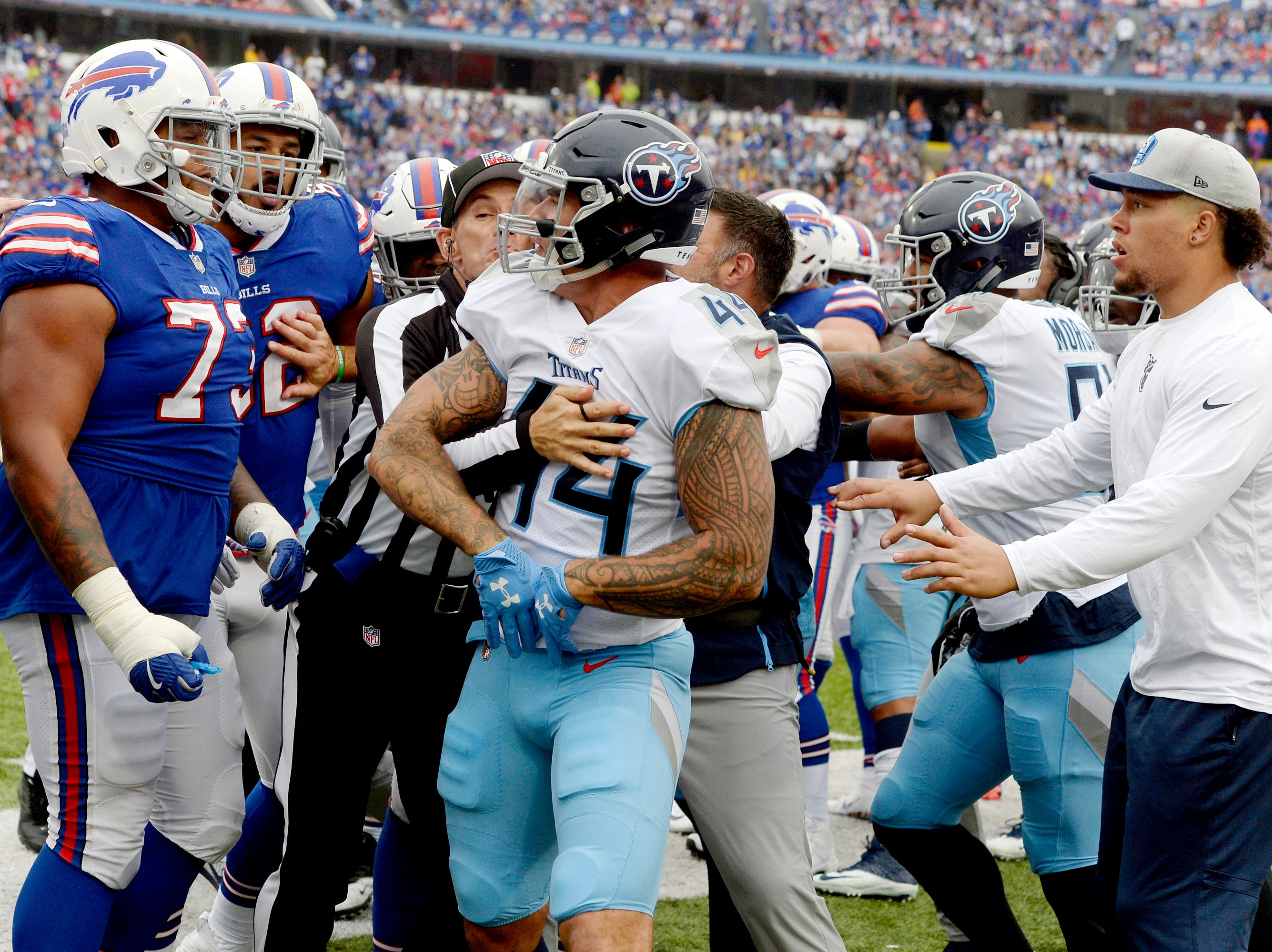 Tennessee Titans linebacker Kamalei Correa (44) is held back by head coach Mike Vrabel as he argues with Buffalo Bills offensive tackle Dion Dawkins (73) during the second half of an NFL football game, Sunday, Oct. 7, 2018, in Orchard Park, N.Y. (AP Photo/Adrian Kraus)