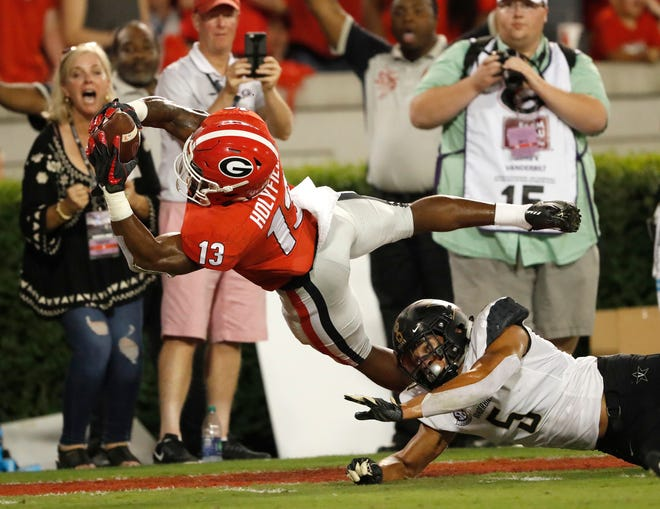 Georgia running back Elijah Holyfield (13) dives into the end zone for a touchdown as Vanderbilt safety LaDarius Wiley (5) defends during the first half of an NCAA college football game Saturday, Oct. 6, 2018, in Atlanta. (AP Photo/John Bazemore)