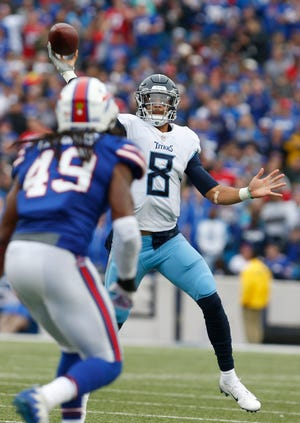 Titans quarterback Marcus Mariota (8) throws a pass against the Bills and linebacker Tremaine Edmunds on Sunday.