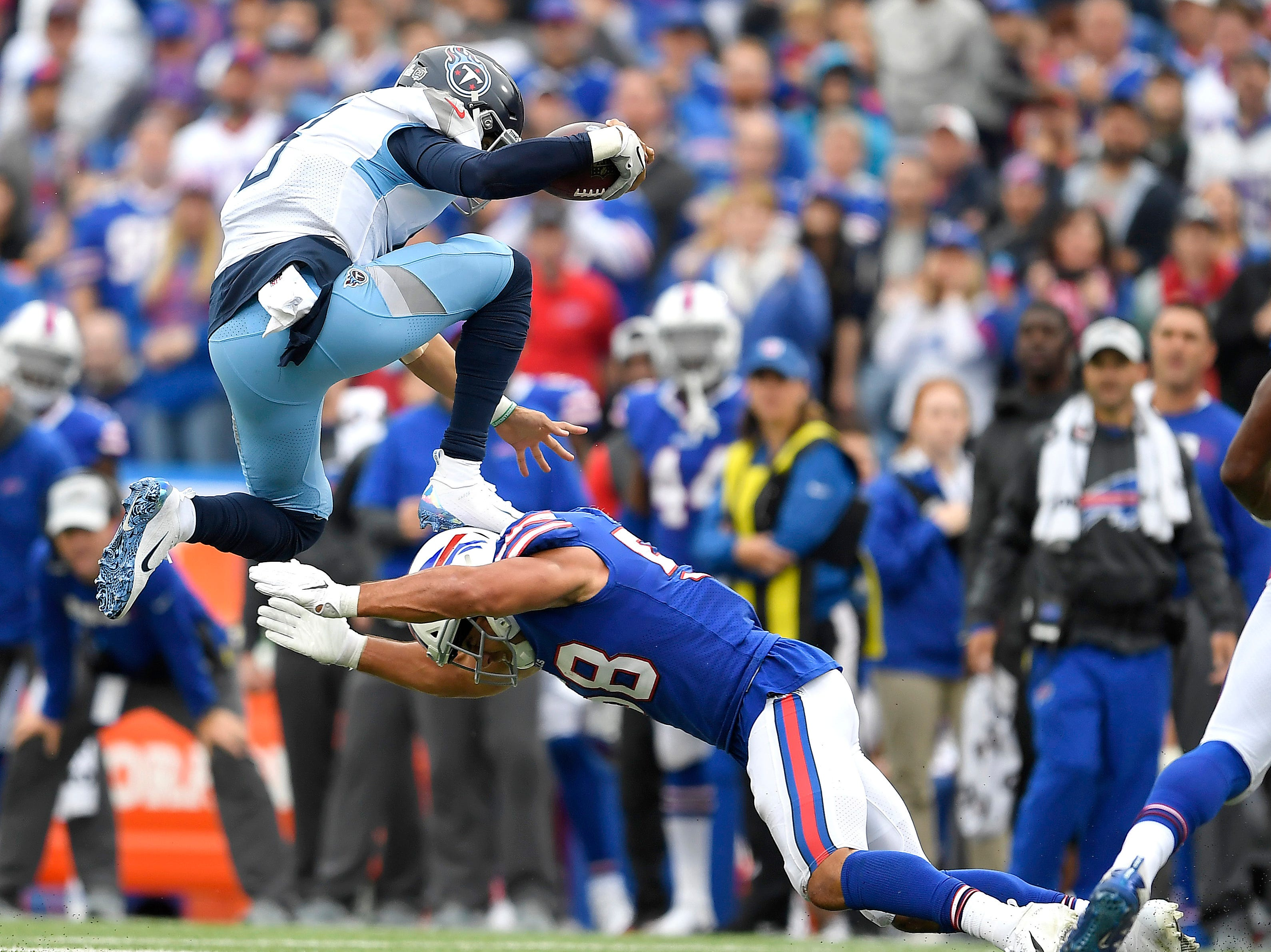 Tennessee Titans quarterback Marcus Mariota, top, leaps over Buffalo Bills linebacker Matt Milano during the second half of an NFL football game, Sunday, Oct. 7, 2018, in Orchard Park, N.Y. (AP Photo/Adrian Kraus)