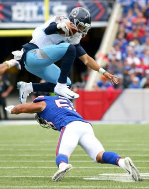 Titans quarterback Marcus Mariota, top, leaps over Bills linebacker Matt Milano while running for a first down during the second half Sunday.