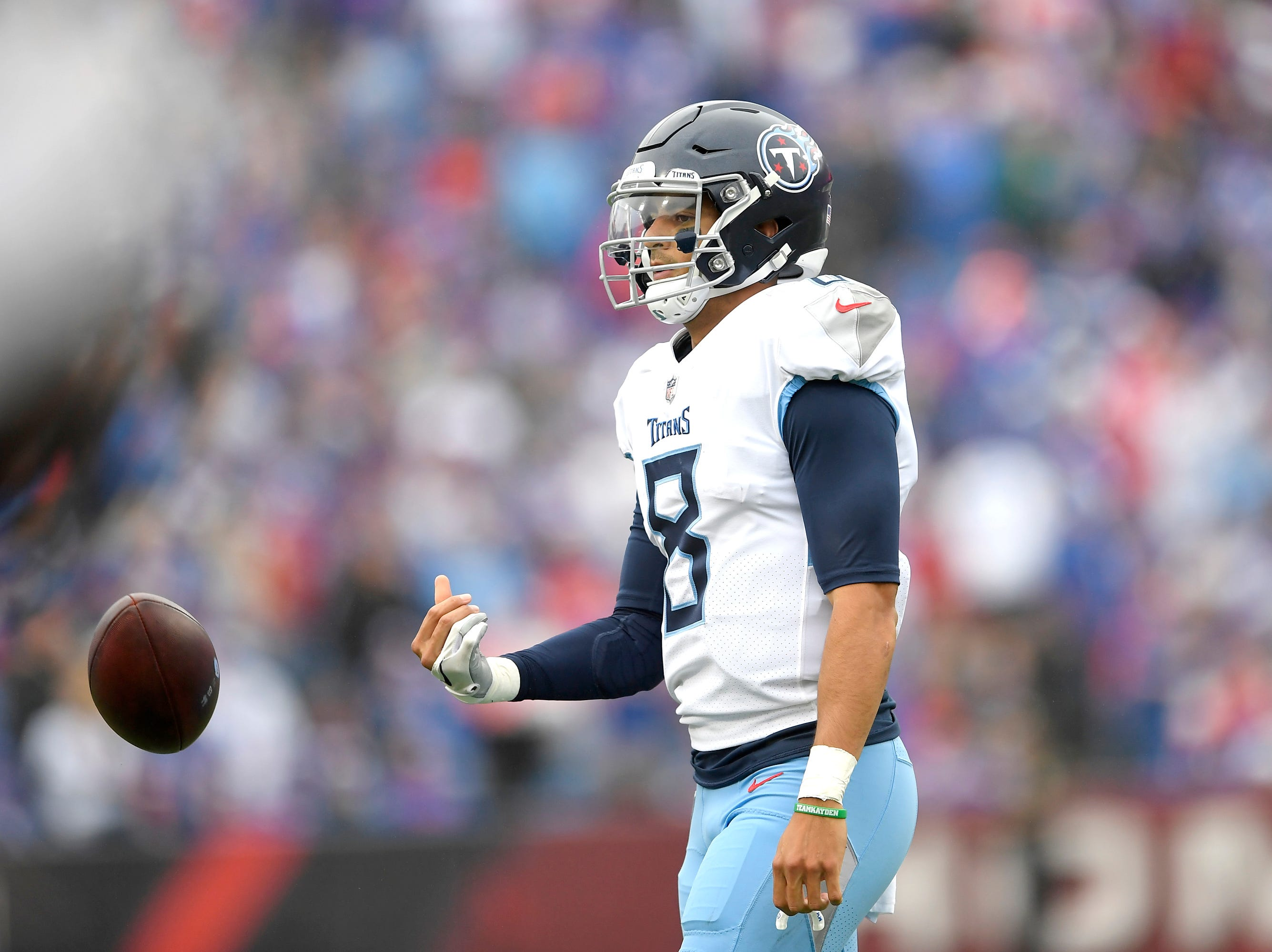 Tennessee Titans quarterback Marcus Mariota tosses the ball to an official after being brought down by Buffalo Bills defenders during the first half of an NFL football game, Sunday, Oct. 7, 2018, in Orchard Park, N.Y. (AP Photo/Adrian Kraus)