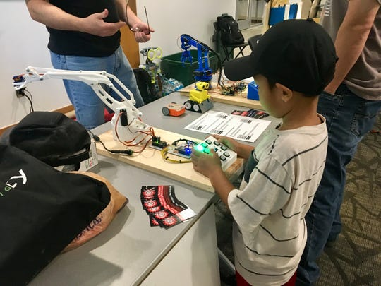 A youngster tries out a robot at the Nashville Mini Maker Faire at Vanderbilt University on Sunday, Oct. 7, 2018.
