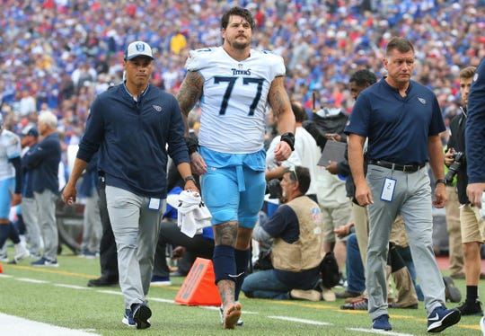 Titans offensive tackle Taylor Lewan (77) walks off the field after suffering an injury in the second quarter Sunday.