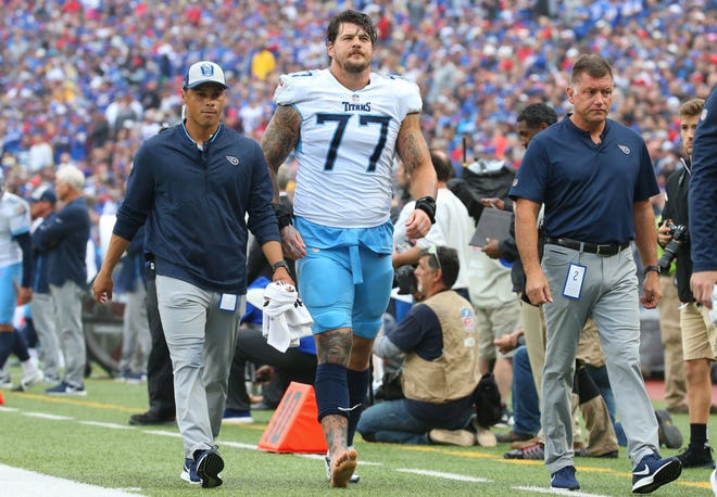 Titans offensive tackle Taylor Lewan (77) walks off the field after suffering an injury against the Bills during the second quarter Sunday.