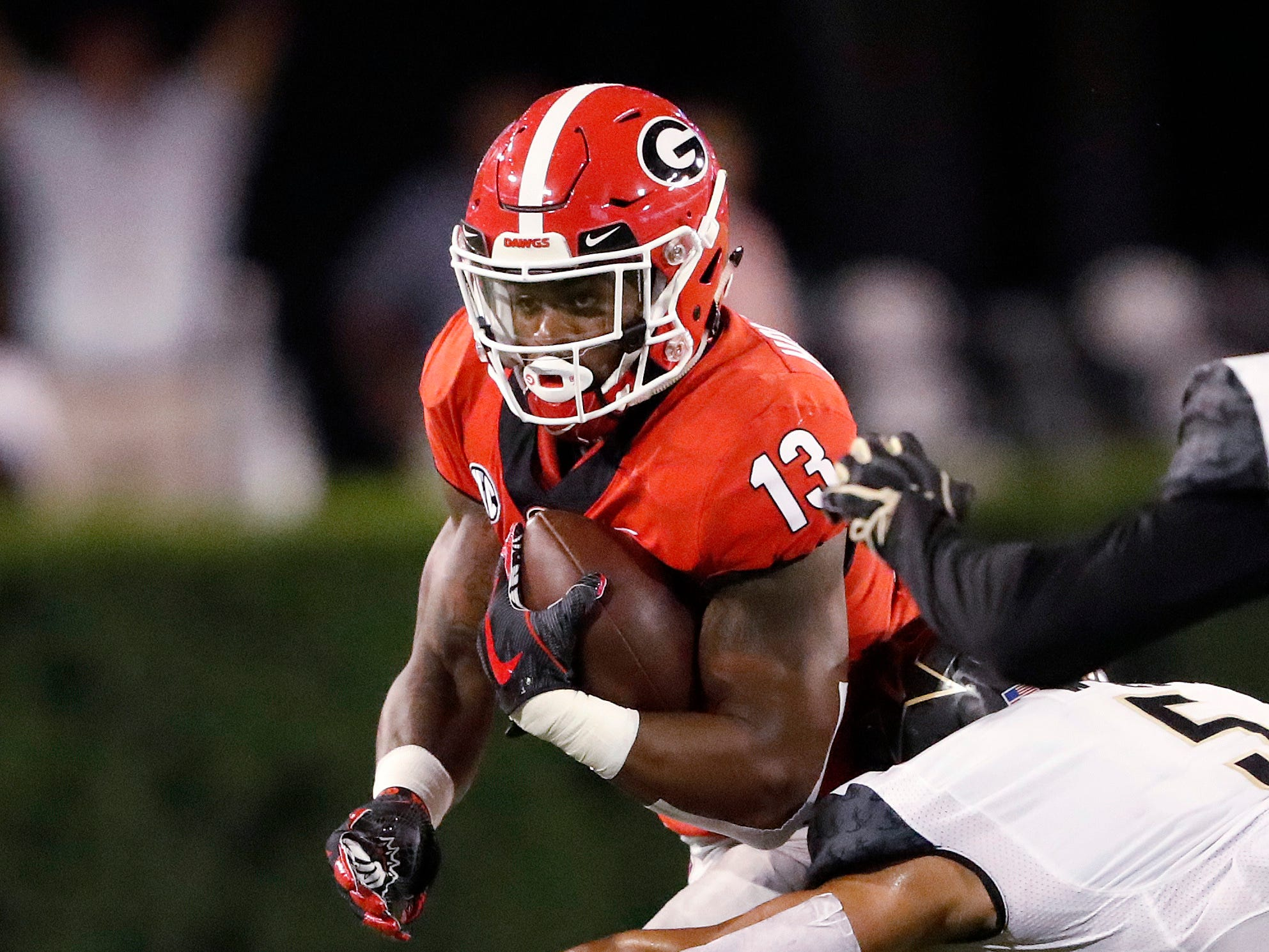 Georgia running back Elijah Holyfield (13) tries to get past Vanderbilt safety LaDarius Wiley (5) during the first half of an NCAA college football game Saturday, Oct. 6, 2018, in Atlanta. (AP Photo/John Bazemore)