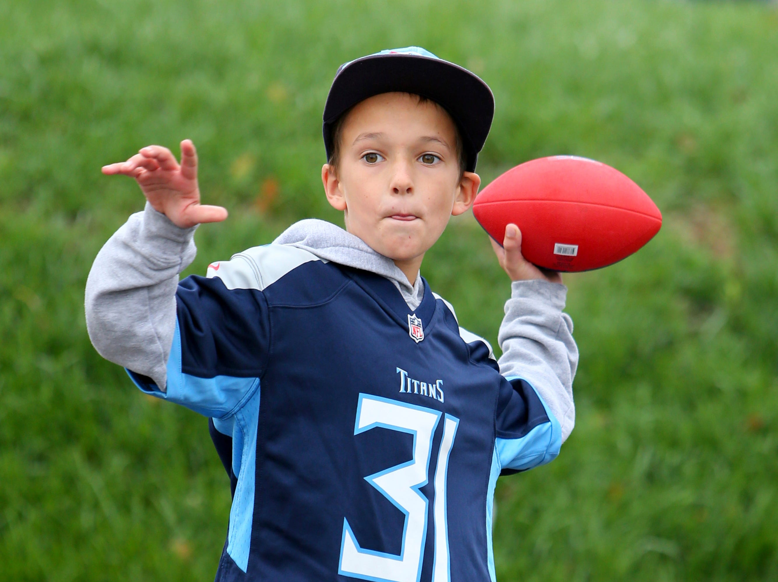 Wyatt Brockman, of Nashville, Tenn., throws a football while tailgating at New Era Field prior to an NFL football game between the Buffalo Bills and the Tennessee Titans, Sunday, Oct. 7, 2018, in Orchard Park, N.Y. (AP Photo/Jeffrey T. Barnes)