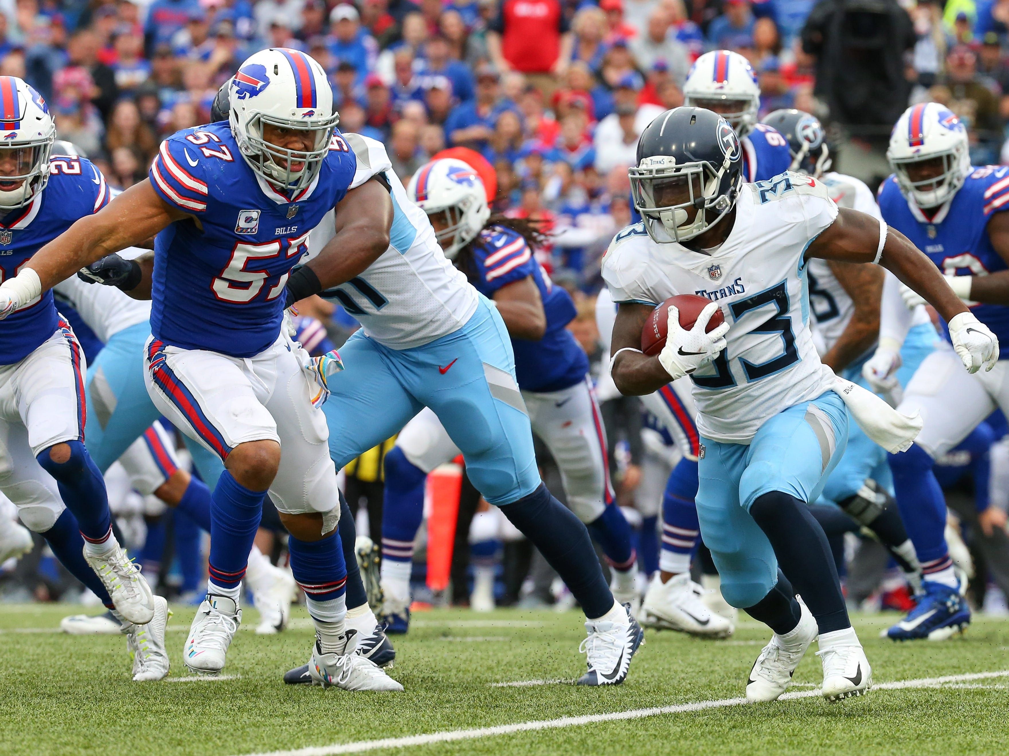 Oct 7, 2018; Orchard Park, NY, USA; Tennessee Titans running back Dion Lewis (33) runs with the ball against Buffalo Bills linebacker Lorenzo Alexander (57) during the third quarter at New Era Field.