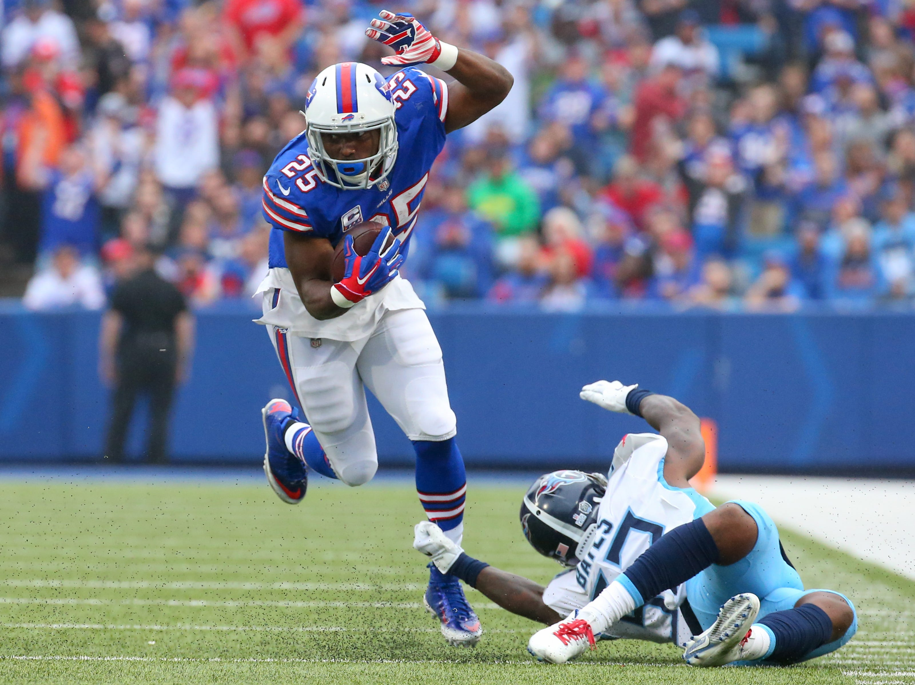 Oct 7, 2018; Orchard Park, NY, USA; Buffalo Bills running back LeSean McCoy (25) runs with the ball while avoiding a tackle attempt by Tennessee Titans linebacker Daren Bates (53) during the second quarter at New Era Field.