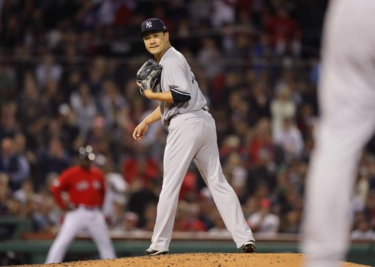 BOSTON, MA - OCTOBER 06:  Pitcher Masahiro Tanaka #19 of the New York Yankees looks back at first base to check runner Jackie Bradley Jr. #19 of the Boston Red Sox  (not in photo) during the third inning of Game Two of the American League Division Series against the Boston Red Sox at Fenway Park on October 6, 2018 in Boston, Massachusetts.