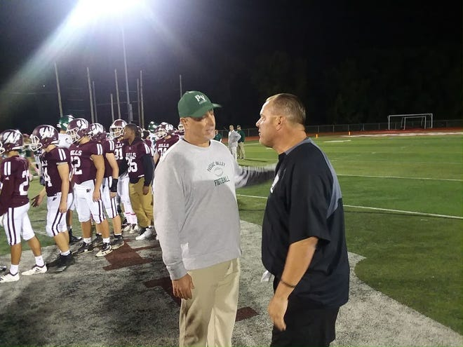 Passaic Valley coach Chet Parlavecchio (left) and Wayne Hills coach Wayne Demikoff meet following the Passaic Valley at Wayne Hills football game Oct. 5.