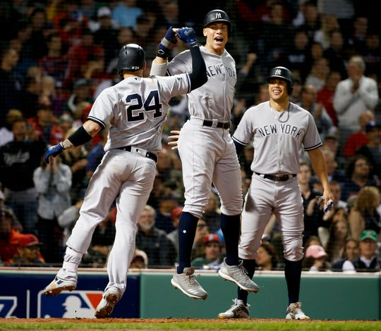 New York Yankees' Gary Sanchez, left, celebrates after his three-run home run against the Boston Red Sox with Aaron Judge and Giancarlo Stanton during the seventh inning of Game 2 of a baseball American League Division Series, Saturday, Oct. 6, 2018, in Boston.